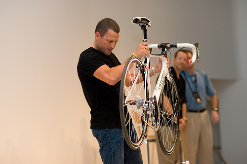Lance Armstrong checks his bew bike, the PM is in the shadows-jpg